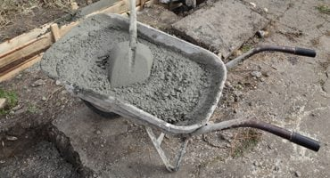 betonmortel lossen in kruiwagen